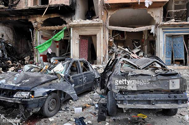 A picture taken on February 21 2016 shows damaged cars at the site of a double car bomb attack in the AlZahraa neighborhood of the central Syrian...