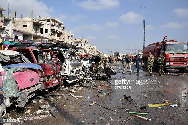 A picture taken on February 21 2016 shows damaged vehicles at the site of a double car bomb attack in the AlZahraa neighborhood of the central Syrian...