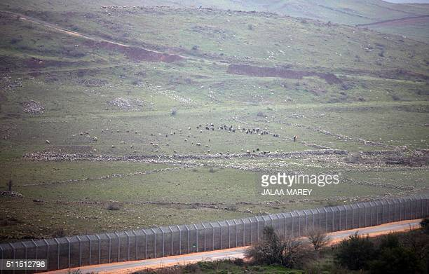 A picture taken on February 21 from the Israeliannexed Syrian Golan Heights shows a section of the border fence between the Golan Heights and Syria...