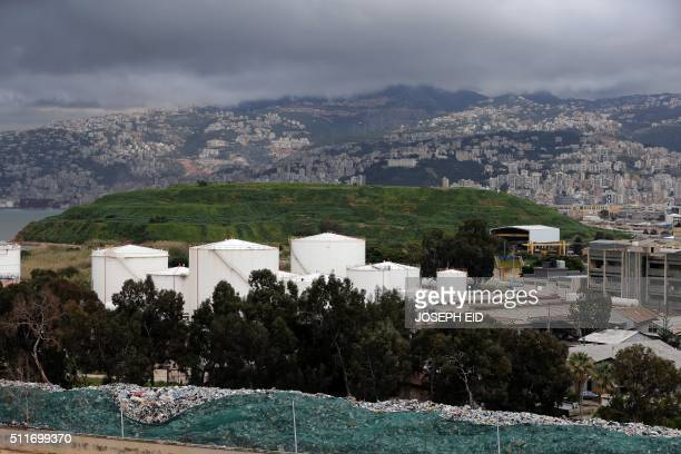 A picture taken on February 22 2016 shows waste on the sides of the river in Beirut in the foreground and green grass covering the closed Karantina...