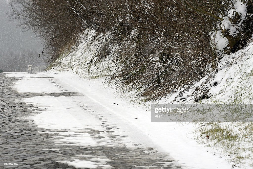 A picture taken on February 24, 2013 shows the Oude Kwaremont hill and its cobblestones road ahead of the 66th edition of the Kuurne-Brussels-Kuurne one-day cycling race on February 24 2013, in Kuurne. The organisation decided to cancel the race as the snowfall and freezing temperatures made the track too dangerous. (placard on fence reads 'cycling race').