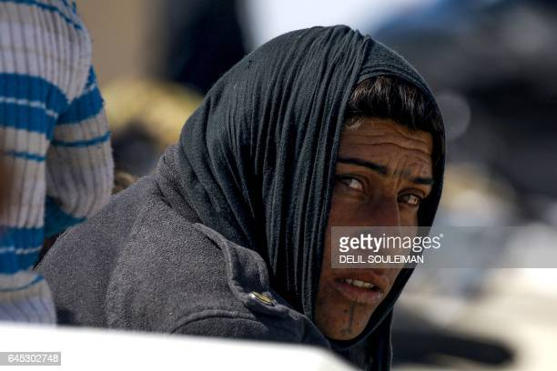TOPSHOT A picture taken on February 25 2017 shows an Iraqi refugee who fled from Mosul sitting in a camp in alHol located some 14 kilometers from the...