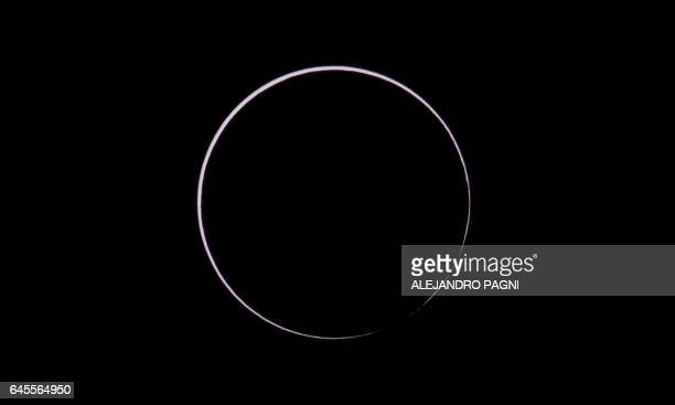 Picture taken on February 26 2017 showing the moon moving to cover the sun for an annular solar eclipse as seen from the Estancia El Muster near...