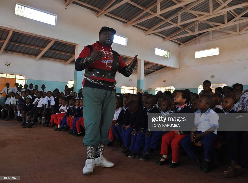 A picture taken on February 28, 2013 shows Conrad Njeru Karukenya, 67, aka 'Tiger-power' during a presentation to pupils of the Tenri primary school in Kenya's central highlands county of Embu, which is also his place of birth. This living, breathing speed bump is a local legend and has a stomach that is strong enough to withstand a Land Rover running right over him, according to Discovery channel's Quest tv, hosted in the United Kingdom, which in May of last year hosted what has popularly been dubbed a 'superhuman showdown' that featured seemingly regular human beings with incredible abilities in a contest for the title of ultimate Superhuman. Divided into five unifying traits: speed, strength, endurance, brain power and skill five contestants push themselves to the limit in each episode, with Conrad placed second in the strength category, and among five finalists by internationally-acclaimed scientists Dr Heather Berlin, Dr Rahul Jandial and Professor Greg Whyte who will further select the two most impressive individuals to go head to head in the gruelling final showdown. From humble beginnings, the spiritual family man who loves eating organic food and whole grains and has never smoked or indulged in alchohol his entire life says,' I started doing these things as a joke while in school in 1963'. AFP PHOTO /Tony KARUMBA