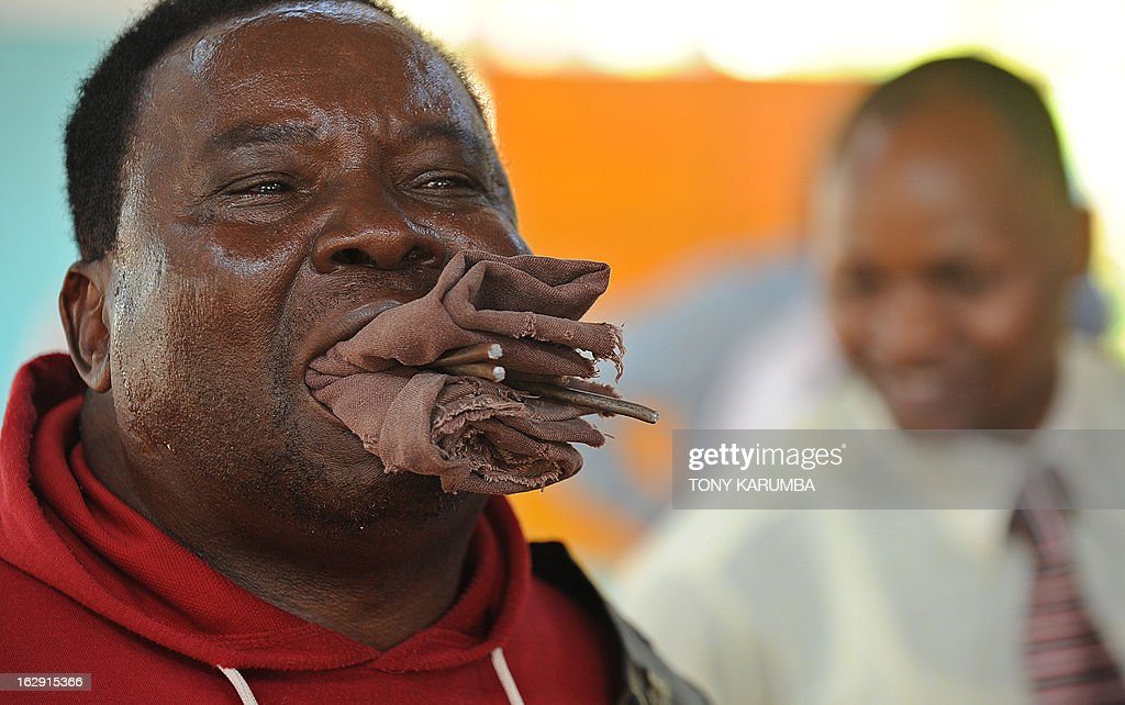 A picture taken on February 28, 2013 shows Conrad Njeru Karukenya, 67, aka 'Tiger-power' holding in his mouth bits of three-six-inch nails that he broke off a plank of wood with his teeth during a presentation to pupils of Tenri primary school in Kenya's central highlands county of Embu, which is also his place of birth. This living, breathing speed bump is a local legend and has a stomach that is strong enough to withstand a Land Rover running right over him, according to Discovery channel's Quest tv, hosted in the United Kingdom, which in May of last year hosted what has popularly been dubbed a 'superhuman showdown' that featured seemingly regular human beings with incredible abilities in a contest for the title of ultimate Superhuman. Divided into five unifying traits: speed, strength, endurance, brain power and skill five contestants push themselves to the limit in each episode, with Conrad placed second in the strength category, and among five finalists by internationally-acclaimed scientists Dr Heather Berlin, Dr Rahul Jandial and Professor Greg Whyte who will further select the two most impressive individuals to go head to head in the gruelling final showdown. From humble beginnings, the spiritual family man who loves eating organic food and whole grains and has never smoked or indulged in alchohol his entire life says,' I started doing these things as a joke while in school in 1963'. AFP PHOTO /Tony KARUMBA