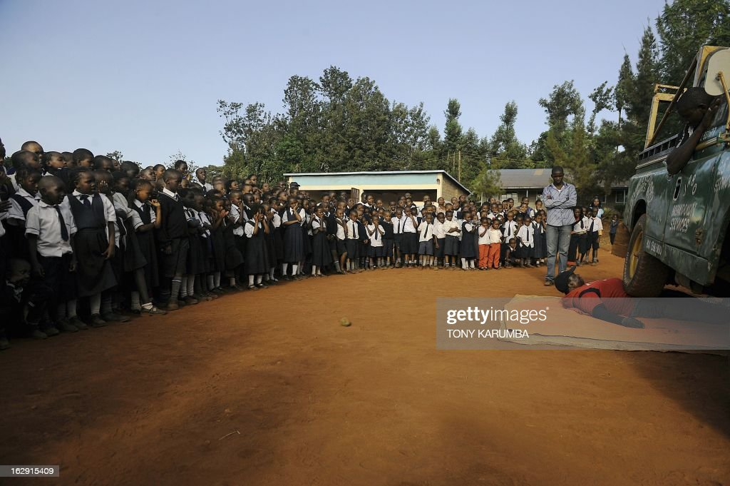 A picture taken on February 28, 2013 shows Conrad Njeru Karukenya (R), 67, aka 'Tiger-power' lying on the ground as a Land Rover runs over his gut during a presentation to pupils of the Tenri primary school in Kenya's central highlands county of Embu, which is also his place of birth. This living, breathing speed bump is a local legend and has a stomach that is strong enough to withstand a Land Rover running right over him, according to Discovery channel's Quest tv, hosted in the United Kingdom, which in May of last year hosted what has popularly been dubbed a 'superhuman showdown' that featured seemingly regular human beings with incredible abilities in a contest for the title of ultimate Superhuman. Divided into five unifying traits: speed, strength, endurance, brain power and skill five contestants push themselves to the limit in each episode, with Conrad placed second in the strength category, and among five finalists by internationally-acclaimed scientists Dr Heather Berlin, Dr Rahul Jandial and Professor Greg Whyte who will further select the two most impressive individuals to go head to head in the gruelling final showdown. From humble beginnings, the spiritual family man who loves eating organic food and whole grains and has never smoked or indulged in alchohol his entire life says,' I started doing these things as a joke while in school in 1963'. AFP PHOTO /Tony KARUMBA