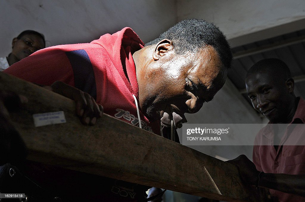 A picture taken on February 28, 2013 shows Conrad Njeru Karukenya, 67, aka 'Tiger-power' attempting to break with his teeth three-six-inch nails from a plank of wood during a presentation to pupils of the Tenri primary school in Kenya's central highlands county of Embu, which is also his place of birth. This living, breathing speed bump is a local legend and has a stomach that is strong enough to withstand a Land Rover running right over him, according to Discovery channel's Quest tv, hosted in the United Kingdom, which in May of last year hosted what has popularly been dubbed a 'superhuman showdown' that featured seemingly regular human beings with incredible abilities in a contest for the title of ultimate Superhuman. Divided into five unifying traits: speed, strength, endurance, brain power and skill five contestants push themselves to the limit in each episode, with Conrad placed second in the strength category, and among five finalists by internationally-acclaimed scientists Dr Heather Berlin, Dr Rahul Jandial and Professor Greg Whyte who will further select the two most impressive individuals to go head to head in the gruelling final showdown. From humble beginnings, the spiritual family man who loves eating organic food and whole grains and has never smoked or indulged in alchohol his entire life says,' I started doing these things as a joke while in school in 1963'. AFP PHOTO /Tony KARUMBA