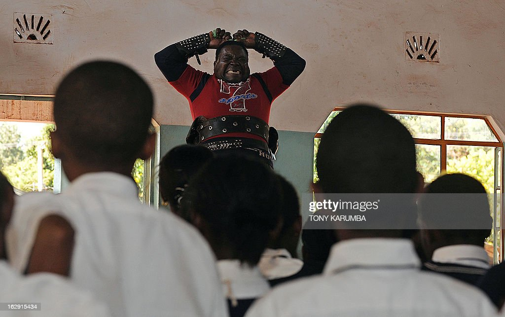 A picture taken on February 28, 2013 shows Conrad Njeru Karukenya, 67, aka 'Tiger-power' attempting to break in-two a six-inch nail with his bare hands during a presentation to pupils of Tenri primary school in Kenya's central highlands county of Embu, which is also his place of birth. This living, breathing speed bump is a local legend and has a stomach that is strong enough to withstand a Land Rover running right over him, according to Discovery channel's Quest tv, hosted in the United Kingdom, which in May of last year hosted what has popularly been dubbed a 'superhuman showdown' that featured seemingly regular human beings with incredible abilities in a contest for the title of ultimate Superhuman. Divided into five unifying traits: speed, strength, endurance, brain power and skill five contestants push themselves to the limit in each episode, with Conrad placed second in the strength category, and among five finalists by internationally-acclaimed scientists Dr Heather Berlin, Dr Rahul Jandial and Professor Greg Whyte who will further select the two most impressive individuals to go head to head in the gruelling final showdown. From humble beginnings, the spiritual family man who loves eating organic food and whole grains and has never smoked or indulged in alchohol his entire life says,' I started doing these things as a joke while in school in 1963'. AFP PHOTO /Tony KARUMBA