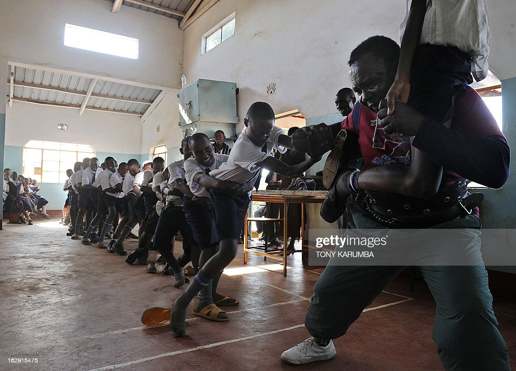 A picture taken on February 28, 2013 shows Conrad Njeru Karukenya, 67, aka 'Tiger-power' engaging students in a one-man-tag-of-war during a presentation to pupils of the Tenri primary school in Kenya's central highlands county of Embu, which is also his place of birth. This living, breathing speed bump is a local legend and has a stomach that is strong enough to withstand a Land Rover running right over him, according to Discovery channel's Quest tv, hosted in the United Kingdom, which in May of last year hosted what has popularly been dubbed a 'superhuman showdown' that featured seemingly regular human beings with incredible abilities in a contest for the title of ultimate Superhuman. Divided into five unifying traits: speed, strength, endurance, brain power and skill five contestants push themselves to the limit in each episode, with Conrad placed second in the strength category, and among five finalists by internationally-acclaimed scientists Dr Heather Berlin, Dr Rahul Jandial and Professor Greg Whyte who will further select the two most impressive individuals to go head to head in the gruelling final showdown. From humble beginnings, the spiritual family man who loves eating organic food and whole grains and has never smoked or indulged in alchohol his entire life says,' I started doing these things as a joke while in school in 1963'. AFP PHOTO /Tony KARUMBA