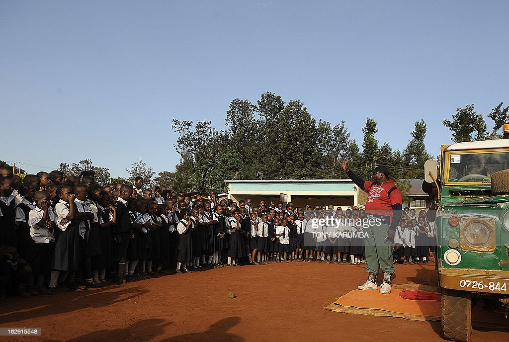 A picture taken on February 28, 2013 shows pupils reacting to a feat of strength by Conrad Njeru Karukenya, 67, aka 'Tiger-power' after a vehicle run over his gut at Tenri primary school in Kenya's central highlands county of Embu, which is also his place of birth. This living, breathing speed bump is a local legend and has a stomach that is strong enough to withstand a Land Rover running right over him, according to Discovery channel's Quest tv, hosted in the United Kingdom, which in May of last year hosted what has popularly been dubbed a 'superhuman showdown' that featured seemingly regular human beings with incredible abilities in a contest for the title of ultimate Superhuman. Divided into five unifying traits: speed, strength, endurance, brain power and skill five contestants push themselves to the limit in each episode, with Conrad placed second in the strength category, and among five finalists by internationally-acclaimed scientists Dr Heather Berlin, Dr Rahul Jandial and Professor Greg Whyte who will further select the two most impressive individuals to go head to head in the gruelling final showdown. From humble beginnings, the spiritual family man who loves eating organic food and whole grains and has never smoked or indulged in alchohol his entire life says,' I started doing these things as a joke while in school in 1963'. AFP PHOTO /Tony KARUMBA
