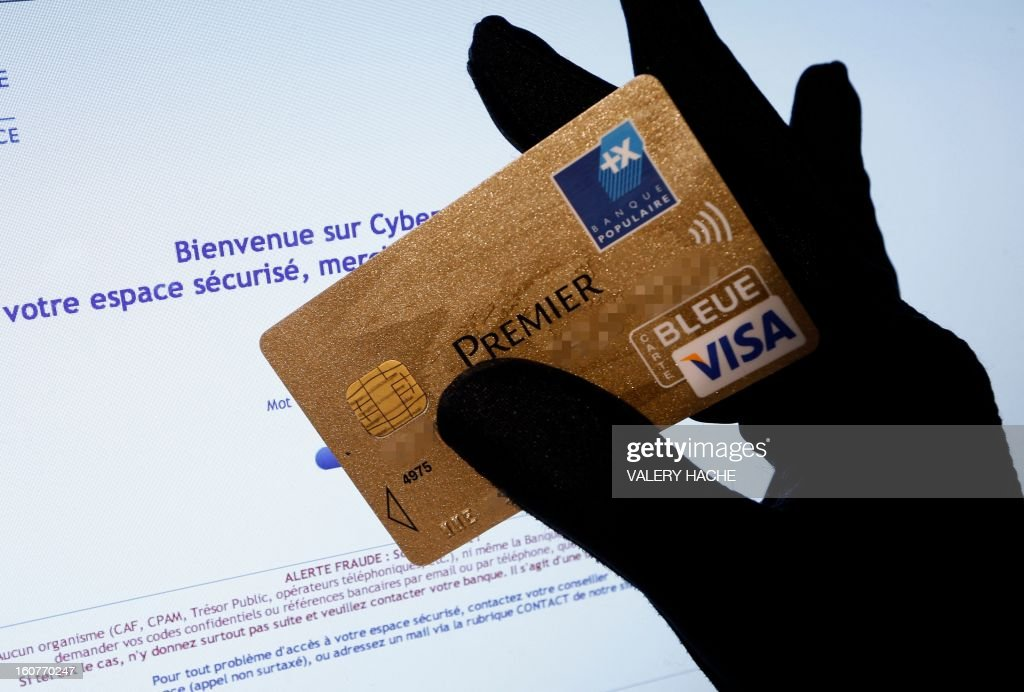 A picture taken on February 5, 2013 in Nice shows a person holding a Visa Premier credit card in front of a computer screen displaying an internet website which bears a warning message against fraud . French police has arrested, early this morning in Paris and in several French and overseas departments, 22 people in connection with the trade of credit cards numbers on internet.