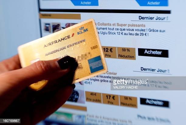 A picture taken on February 5 2013 in Nice shows a person holding an American Express credit card in front of a computer screening displaying the...