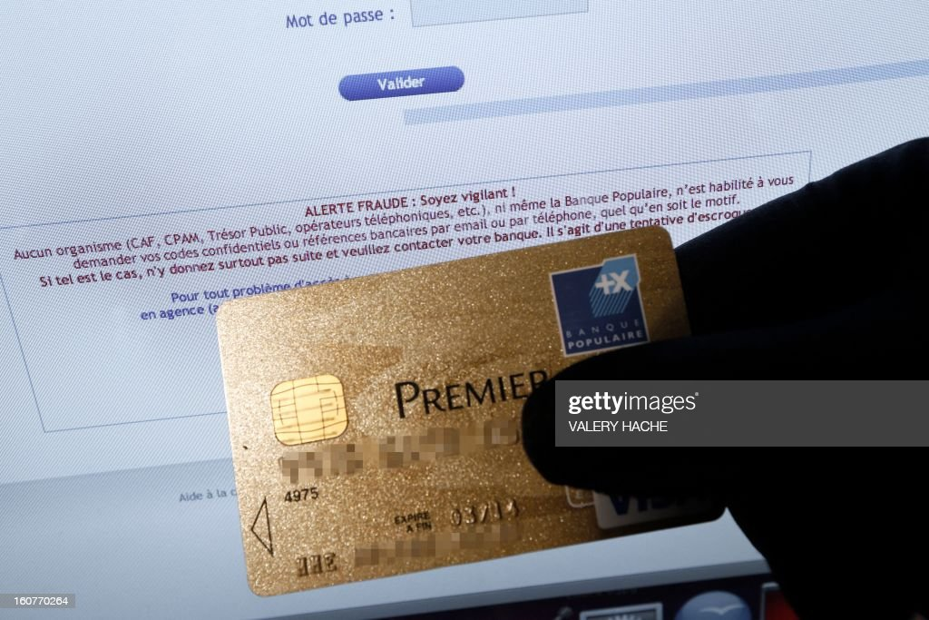 A picture taken on February 5, 2013 in Nice shows a person holding an American Express credit card in front of a computer screen displaying an internet website which bears a warning message against fraud . French police has arrested, early this morning in Paris and in several French and overseas departments, 22 people in connection with the trade of credit cards numbers on internet.