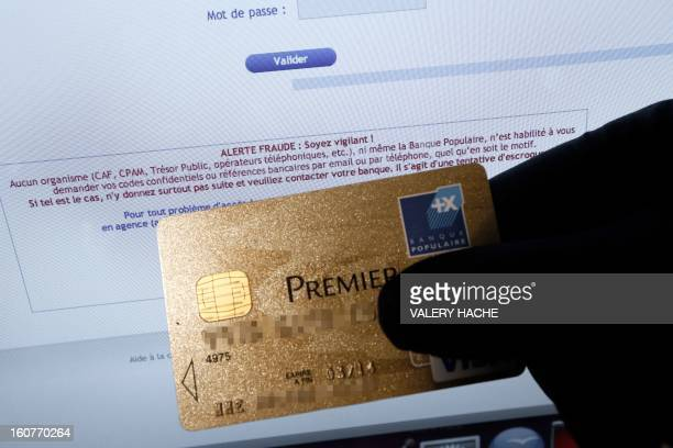 A picture taken on February 5 2013 in Nice shows a person holding an American Express credit card in front of a computer screen displaying an...