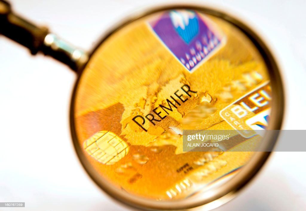 Picture taken on February 5, 2013 in Tours (central France) shows a Visa Premier credit card through a magnifying glass.