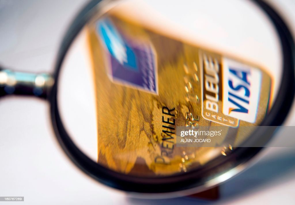 Picture taken on February 5, 2013 in Tours (central France) shows a Visa Premier credit card through a magnifying glass. AFP PHOTO/ ALAIN JOCARD