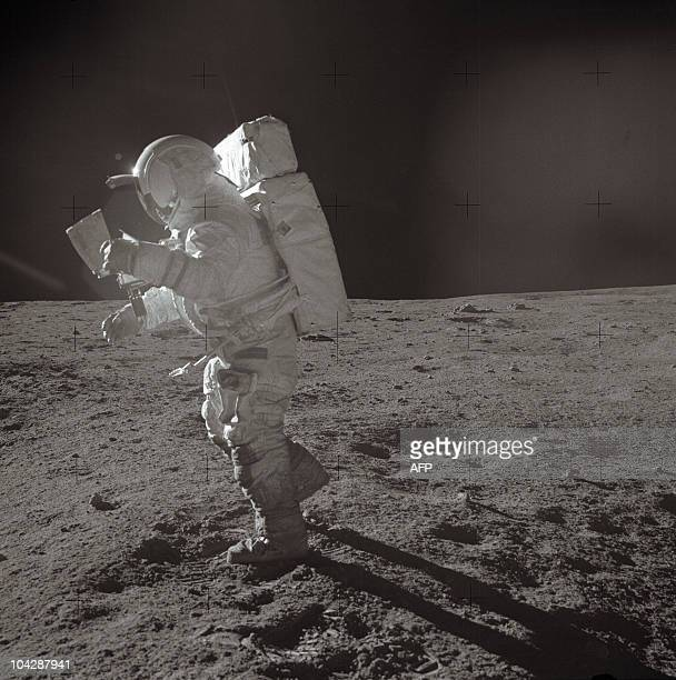 A picture taken on February 6 1971 shows Astronaut Edgar D Mitchell Apollo 14 lunar module pilot moving across the lunar surface while looking over a...