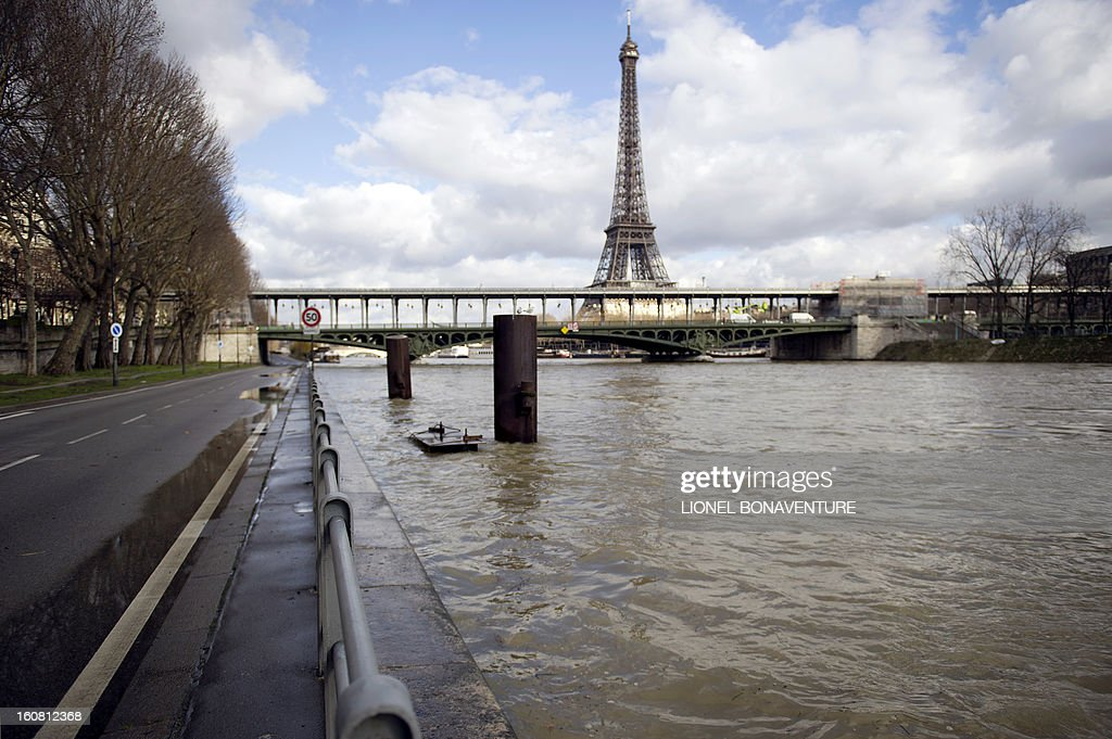 Picture taken on February 6, 2013 shows an overflowing bank of the Seine river as the Eiffel Tower is pictured in the background, in Paris. Roads along the river banks were closed to traffic in case of flooding. AFP PHOTO / LIONEL BONAVENTURE