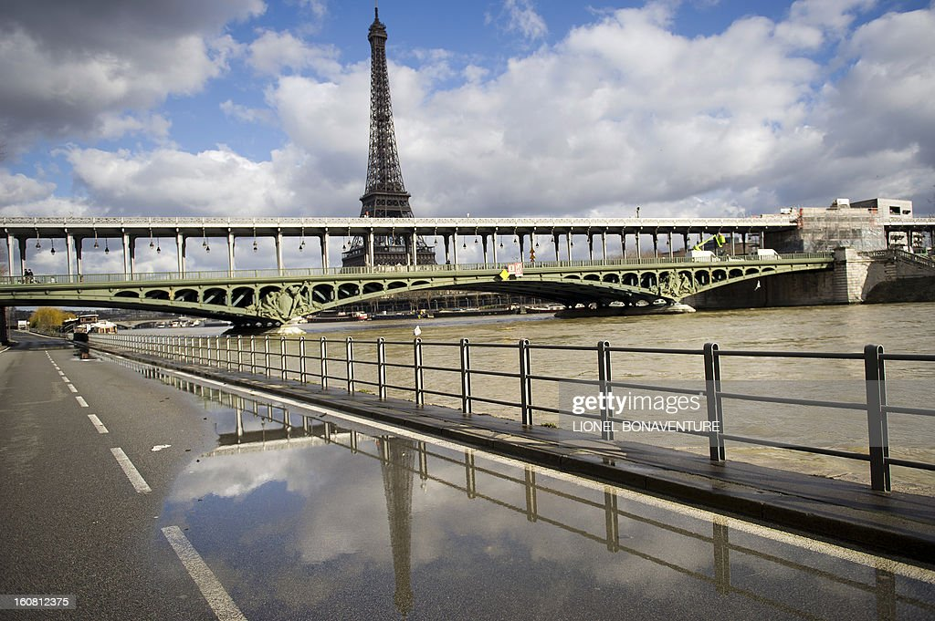 Picture taken on February 6, 2013 shows an overflowing bank of the Seine river as the Eiffel Tower is pictured in the background, in Paris. Roads along the river banks were closed to traffic in case of flooding.