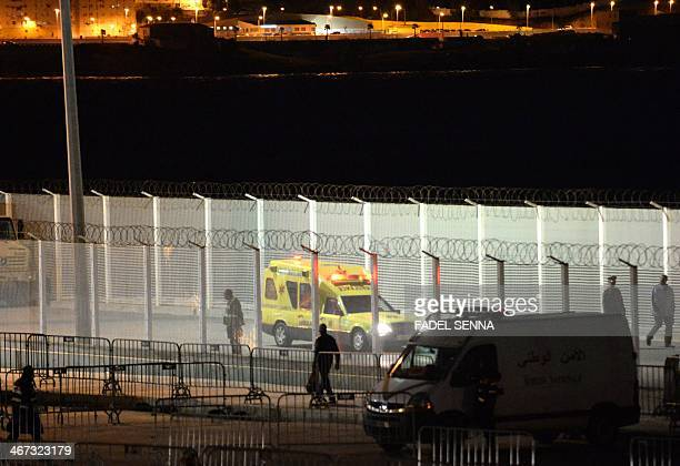 A picture taken on February 6 2014 shows an ambulance loaded with the body of one of the eight migrants who drowned while trying to swim to the...