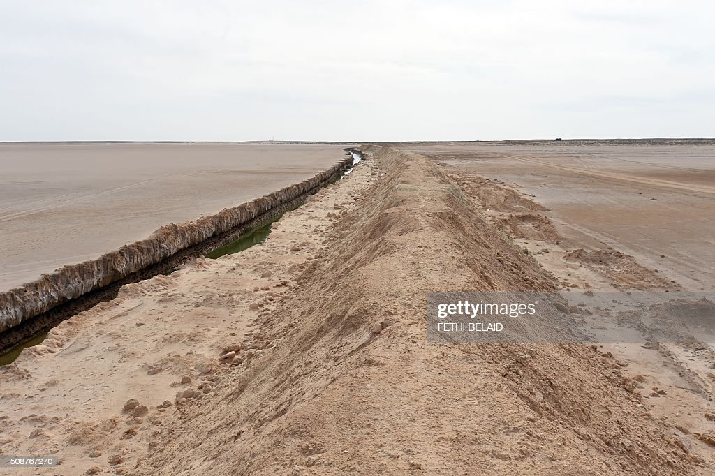 A picture taken on February 6, 2016, shows a trench dug along the Libyan border, near the Ras Jedir crossing point. The construction of a barrier, which includes berms and trenches, along the Libyan border from Ras Jedir on the Mediterranean coast to Dhiba was announced in 2015 after a terrorist attack on the national museum in Tunis killed 22 people. / AFP / FETHI BELAID