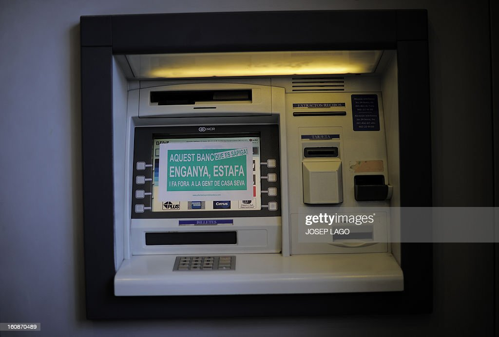 A picture taken on February 7, 2013 shows a sticker reading 'This Bank cheats, swindles and evicts people from their home' on the screen of an ATM machine during a protest against mortgage debt organized by anti-eviction activists of the PAH (the Platform of People Affected by Mortgage) in Barcelona.