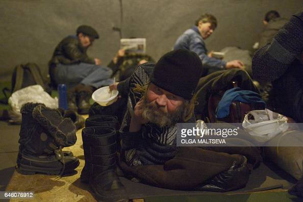 A picture taken on February 7 2017 in Saint Petersburg shows homeless people resting on floor mats as they warm up in a tent set up by Nochlezhka an...