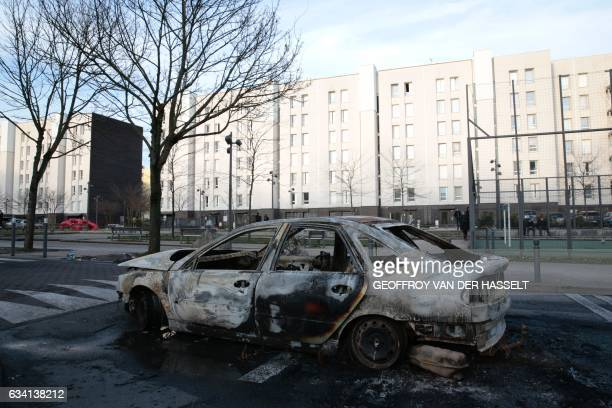 TOPSHOT A picture taken on February 7 2017 shows the wreckage of a burnt car in one of the main streets of the Rose des Vents district also known as...