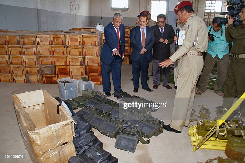 A picture taken on February 8, 2013, in the port of the southern city of Aden, shows a military official showing Yemeni Interior Minister Abdul-Qater Qahtan (L) and other officials binoculars that were found amongst other weapons and military equipment that the Yemeni authorities allegedly seized from a vessel in territorial waters off the coast of Yemen on January 23. UN sanctions experts are investigating the Yemeni government's claims that Iran supplied rockets and explosives seized from a ship last month, diplomats said on February 7.