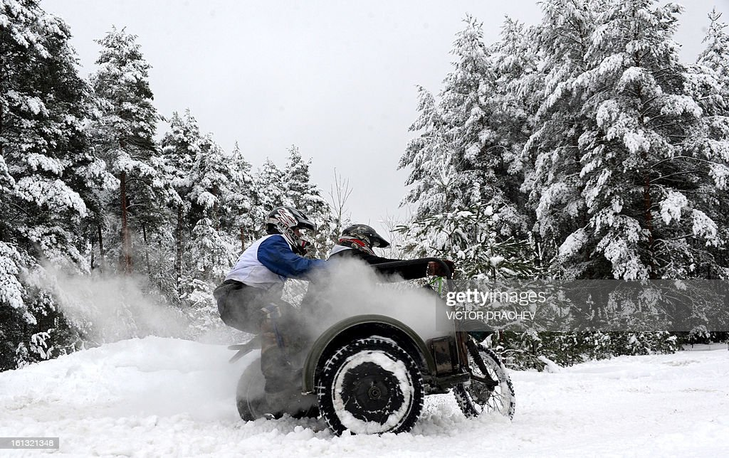 Picture taken on February 9, 2013 shows motocycles amateurs riding a side-cart during a race in a snow covered forest close to Radashkovichi, some 55 km north of Minsk.