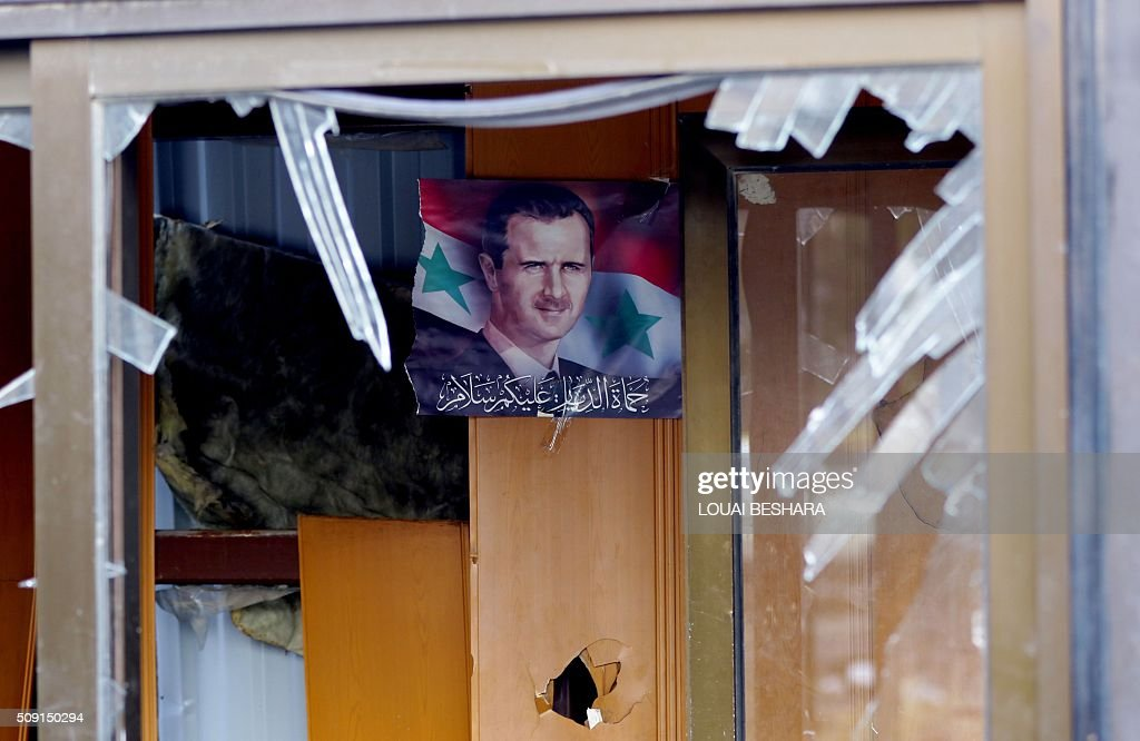 A picture taken on February 9, 2016 shows, through a broken window, a portrait of Syrian President Bashar Assad hanging on a wall in a building next to the site of a suicide attack at a police officer's club in the Masaken Barzeh district of the capital Damascus. The Syrian Observatory for Human Rights said about 20 people had also been wounded, adding that policemen were among the dead and injured. BESHARA
