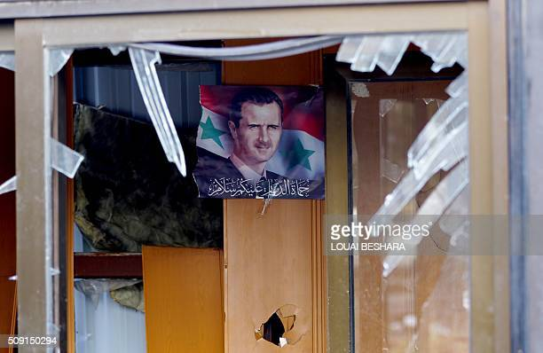 A picture taken on February 9 2016 shows through a broken window a portrait of Syrian President Bashar Assad hanging on a wall in a building next to...