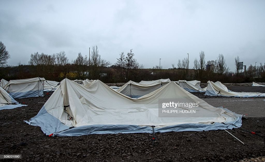 A picture taken on February 9, 2016, shows tents flattened by strong winds after they were set up by humanitarian association 'Medecins du Monde' in Grande-Synthe, northern France, in order to host migrants living in poor conditions in a camp in the city, where nearly 2000 are staying. Two thirds of the tens were damaged in Grande Synthe by strong winds that began hitting the French coast on February 8. / AFP / PHILIPPE HUGUEN