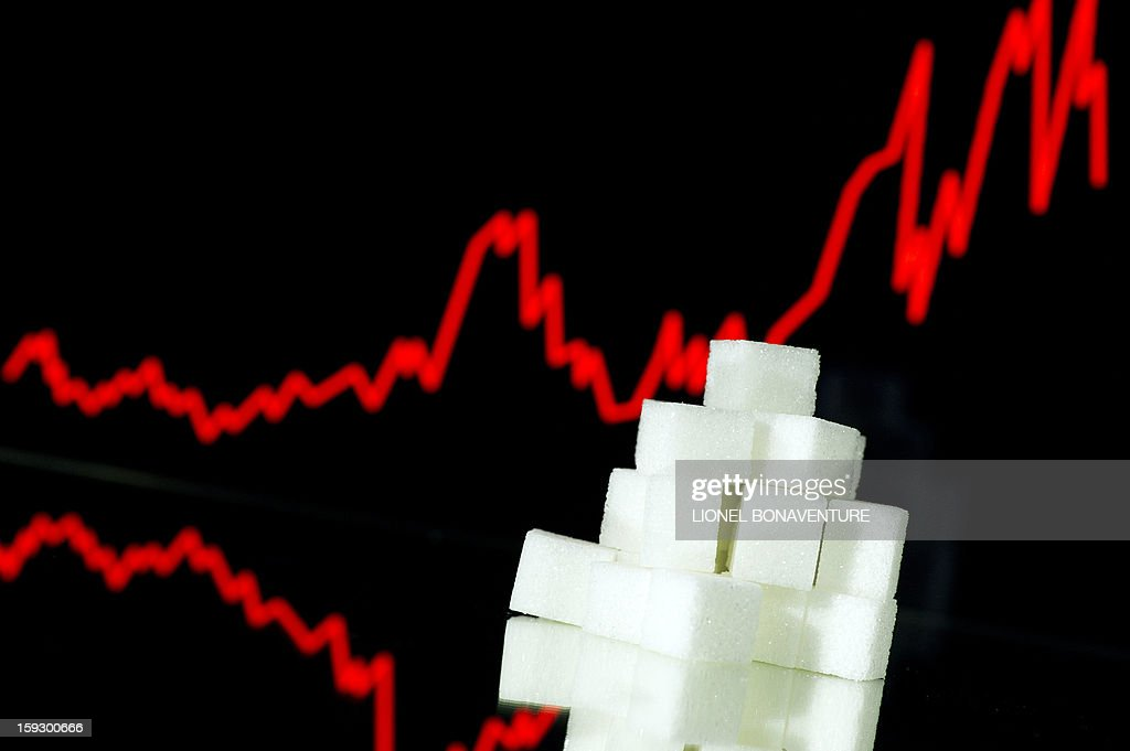 A picture taken on January 10 2013 in Paris shows an illustration made with pieces of white sugar and a screen displaying the sugar exchange rate...