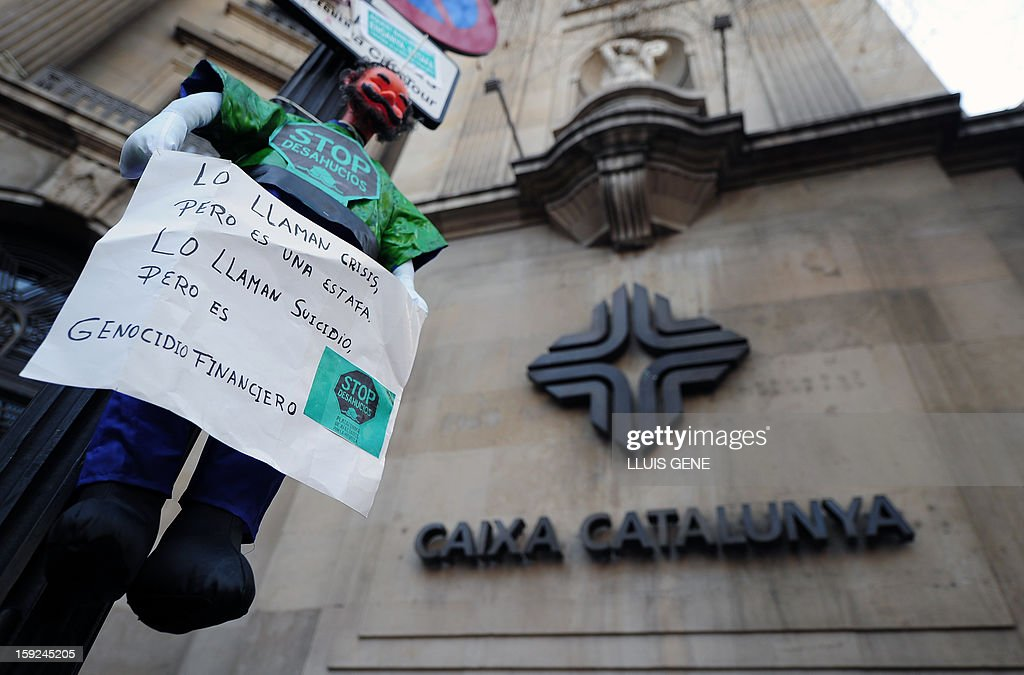 A picture taken on January 10, 2013 shows a figure with a banner reading 'They call it crisis, but this is a fraud, they call it suicide but this is a financial genocide', during a protest against evictions in front of the Catalunya Caixa bank headquarters in Barcelona.