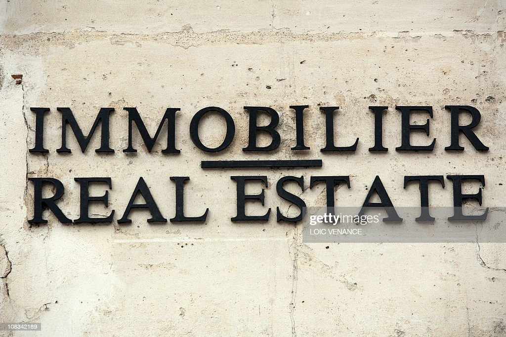 A picture taken on January 13 2011 shows a sign reading Real estate in French and in english AFP PHOTO LOIC VENANCE