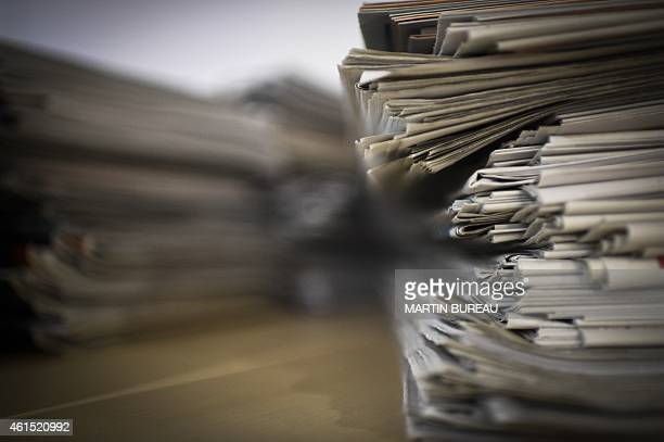 A picture taken on January 14 2015 in Paris shows a pile of newspapers and magazines AFP PHOTO / MARTIN BUREAU