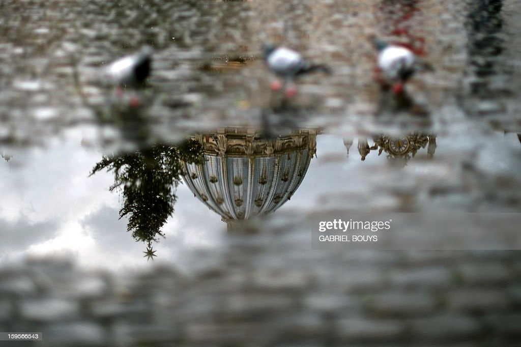 A picture taken on January 16, 2013 in Vatican shows the dome of the Saint Peter Basilica by reflection in a puddle.