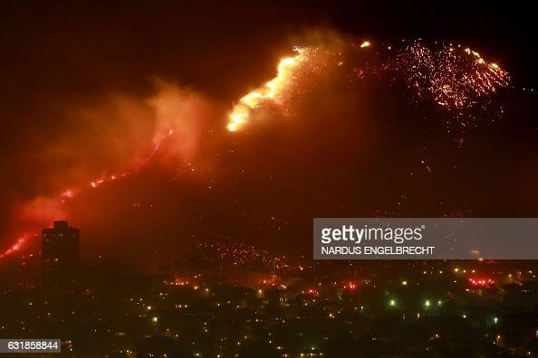TOPSHOT A picture taken on January 17 2016 shows a veld fire spreading on Table Mountain close to the urban side in Cape Town Wildfires have ravaged...