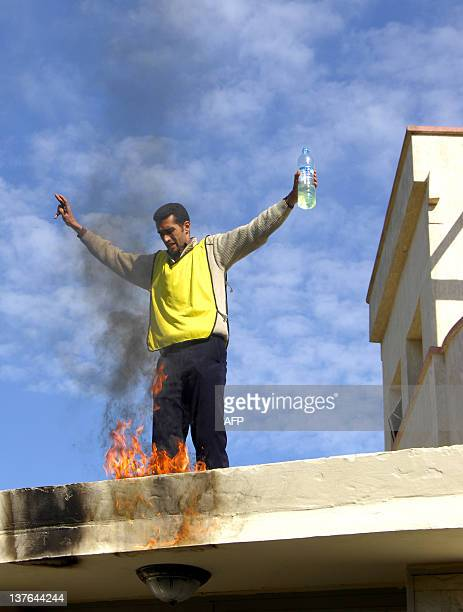 A picture taken on January 18 2012 shows Abdelwahab Zeidoun a young Moroccan unemployed man holding a bottle of petrol amid flames near an education...