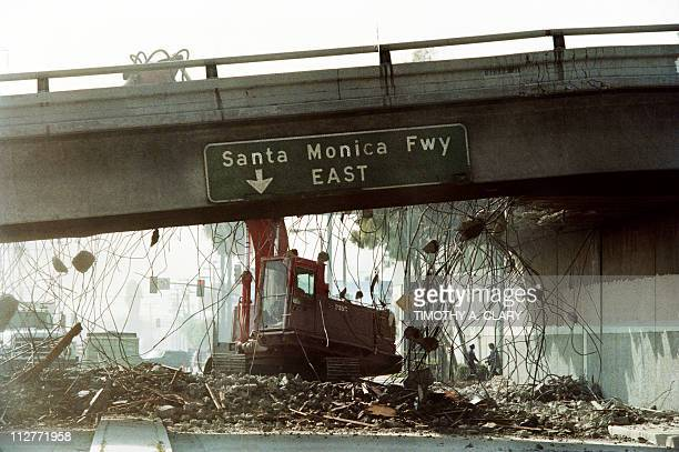 A picture taken on January 19 1994 in Los Angeles California shows a bulldozer tearing down a section of the Santa Monica Freeway that collapsed...