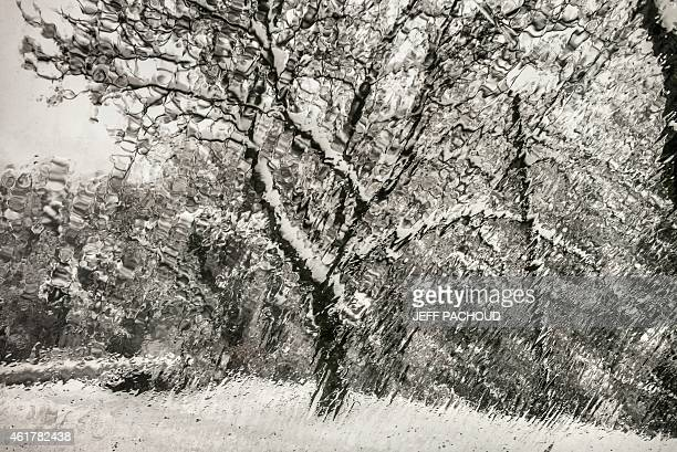 A picture taken on January 19 2015 shows a snowy landscape seen through a window at the Escrinet pass near Privas AFP PHOTO / JEFF PACHOUD