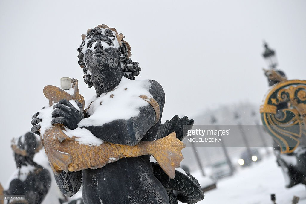 A picture taken on January 20, 2013 in Paris shows a statue of the Place de la Concorde covered with snow during heavy snow falls over the French capital.
