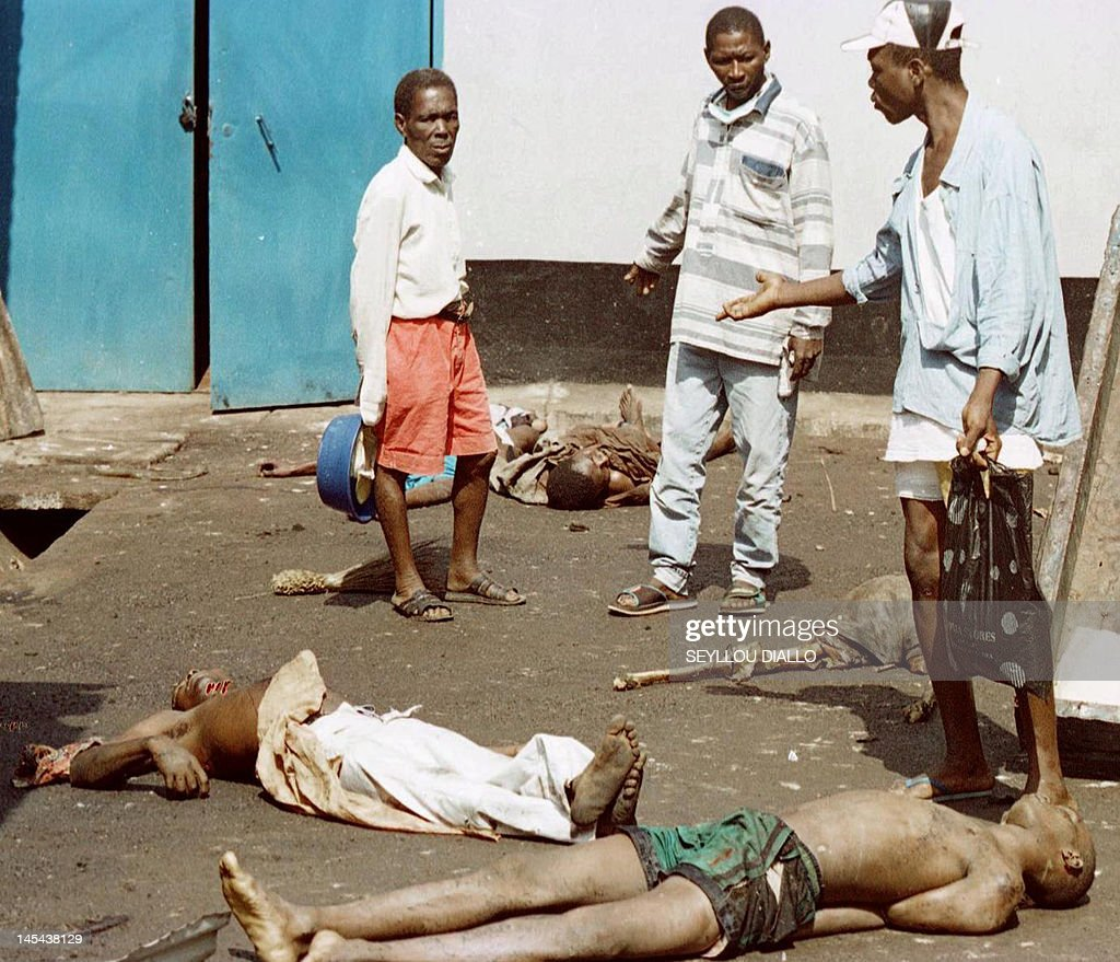 A picture taken on January 22, 1999 shows people standing near abandoned corpses outside a house in Freetownafter tension mounted in the capital, where rebels still threatened some areas despite claims by the Nigerian-led ECOMOG intervention force that it had cleared the city of all insurgents. Former Liberian president Charles Taylor will be sentenced for war crimes by a UN court on May 30, 2012 after being convicted for arming Sierra Leone rebels in return for 'blood diamonds'. Special Court for Sierra Leone judge Richard Lussick will deliver the ruling at a hearing due to start at 0900 GMT, the first sentence against a former head of state at an international court since the Nazi trials at Nuremberg in 1946.