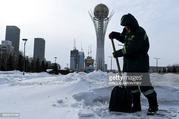 A picture taken on January 22 2017 shows a street cleaner removing show in front of the Bayterek monument in downtown Astana The socalled Astana...