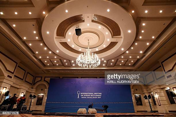 A picture taken on January 22 2017 shows men at work to prepare the Syria peace talks conference room at Astana' Rixos President Hotel The talks set...