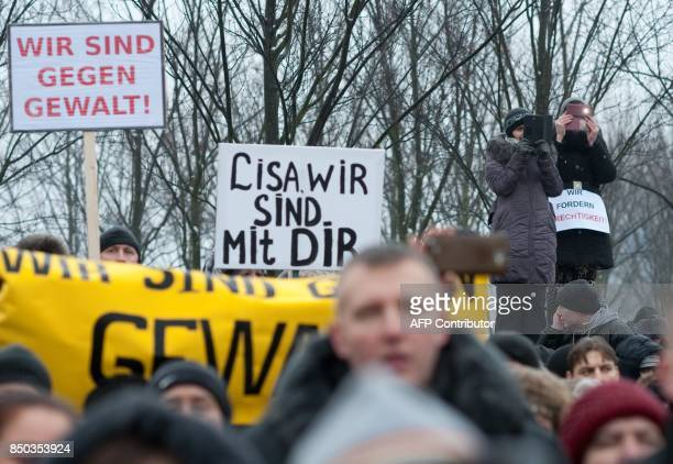 Picture taken on January 23 2016 shows Protesters holding up a sign reading 'Lisa we are with you' as they demonstrate in front of the chancellery...