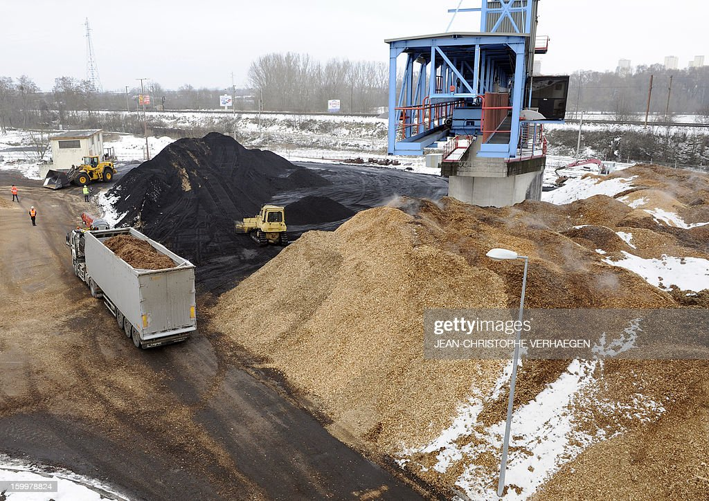 A picture taken on January 24, 2013 shows the storage of fuel composed of wood chips (foreground) to be used for the UEM (Usine d'Electricité de Metz) biomass plant, and of coal (L) to be used for the UEM coal-fired plant in Metz, eastern France. This thermal power plant, coal-fired, gas and biomass, provides electricity and heat to Metz and to the surrounding towns.