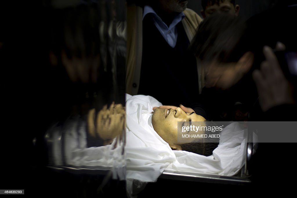 A picture taken on January 24, 2014 at the morgue of Beit Lahia's hospital, northern Gaza Strip shows the body of Bilal Samir Oweida, a 20-year-old Palestinian who was shot dead by Israeli forces after they said he had entered 'a prohibited area'. Bilal Samir Oweida died after being 'shot in the chest by Israeli soldiers' east of Jabaliya, in northern Gaza, said Ashraf al-Qudra, a spokesman for the Hamas-run health ministry.