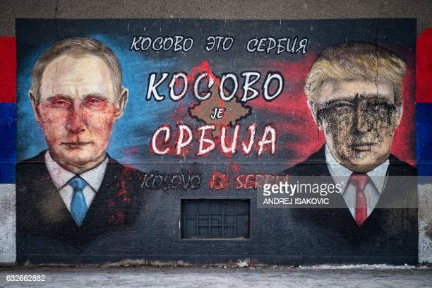TOPSHOT A picture taken on January 25 2017 shows a mural vandalized with paint depicting Russian President Vladimir Putin and US President Donald...